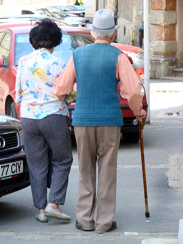 An elderly couple walk together.