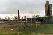 Older sports stadium, with football match in progress