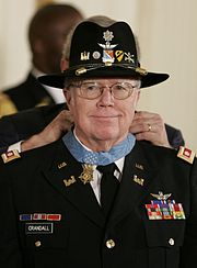 A color picture if Bruce Campbell in his dress military uniform and cavalry hat. He is smiling and President Bush can be seen putting the Medal of Honor around his neck.