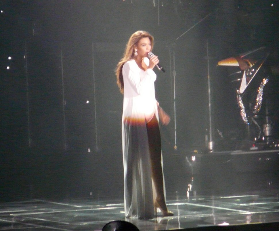 A woman is standing and singing. She wears a white suit with a long cape, and heels. In the background, some musical instruments are visible.