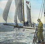"""Håndkolorert dias. Redningsskøyta """"Svolvær"""" seiler. I forgrunnen står en mann kledd i oljehyre og sydvest ombord i en annen båt. (9456256001).jpg"""