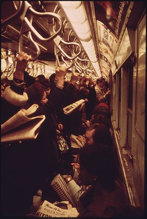 Standing passenger - Passengers using pivoted grab handles on a congested subway train
