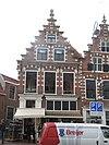 foto van Pand met trapgevel, rijk met natuursteenversieringen voorziene blokken, consoles met engelenmaskers, bogen boven de vensters dragend