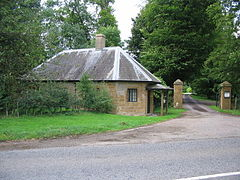 Small building to the left of gateposts surrounded by trees