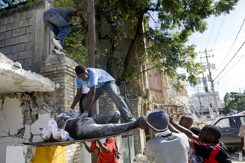 Haitians pull out a body from the rubbles of a school (12 january 2010)