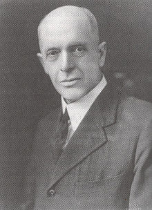 A portrait of a balding white man in a suit