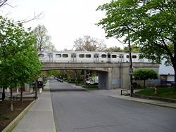 A subway train crosses Clendennan Avenue, a residential road in High Park North