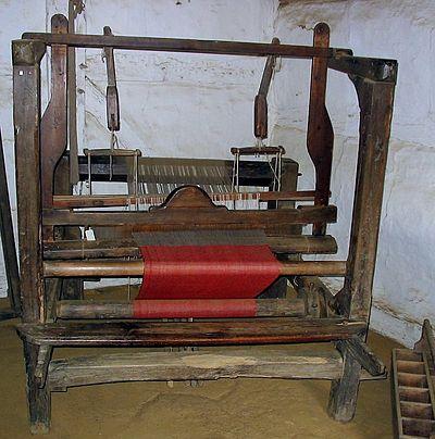 Hand loom at Hjerl Hede en Dinamarca, dispositivo para tejer, con producción de tejidos en diversos colores.
