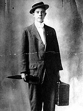 Long dressed in a suit, wearing a straw-hat and carrying an umbrella and a suitcase