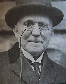 Smiling old man with round glasses wearing a hat