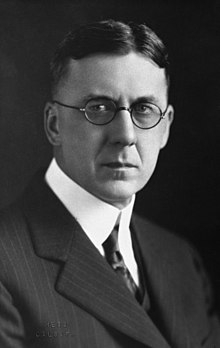 A severe-looking man in round-rimmed glasses