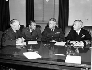 Four men in uniforms but no hats sit at a large polished wood table on which there are pencils, notepads and glass ash trays.