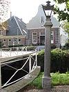 foto van Naast de brug ten westen van de kerk een hardstenen lantaarnpaal