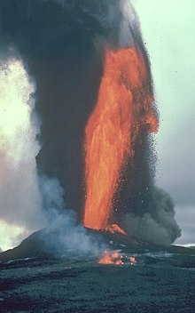 A jet of fluid lava spraying into the air on an island. Smoke rises behind it.