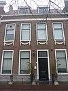 foto van Pand met brede bakstenen gevel, rechte kroonlijst, zandstenen architraaf tussen vensters, festoenen. Hardstenen stoep met palen, gerestaureerd 1937, zadeldak modern