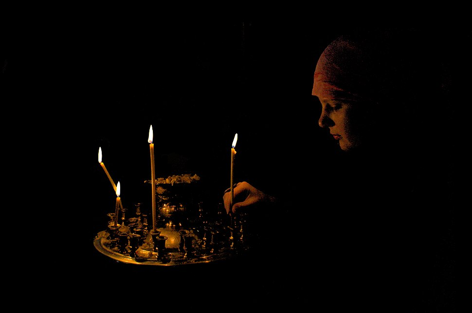 Lighting a candle in Orthodox church, Ukraine