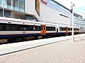London - Shepherd's Bush railway station with train, and Westfield Shopping Centre.jpg