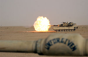 Bore evacuator - Foreground, a close-up of the bore evacuator on an M1 Abrams, while another tank fires in the background