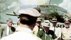 We see the back of MacArthur's head. Truman in a dark suit and light hat stands at a microphone. Behind him stands four mean in shirts and ties. In the background are some onlookers and a sleek metal but propeller driven airliner. Another aircraft lies parked on the runway.