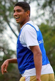 A smiling man with short and dark hair wears a white T-shirt under a blue training vest and pale yellow pants.