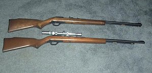 "Marlin Model 60 - Two Marlin Model 60s. Top: older 18-round model. Bottom: 15-round model with aftermarket scope (and magazine tube that is visibly shorter than the barrel).  Note: the bolt stays open on the 15-round model after the last round is fired, but does not on the 18-round model.  The 15 round model has a third screw slightly behind the trigger guard to reinforce the stock, which the old model lacks.  There are a few 1985 models that were a mixture of both, 22"" barrel, 18 round capacity, last round bolt hold open feature and the third reinforcing screw. Different wood is used for the stock itself."