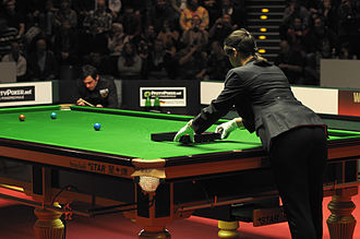 Michaela Tabb - Tabb uses a triangle to rack the reds. In the background Ronnie O'Sullivan.
