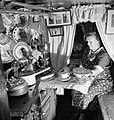 Mrs Skinner prepares the evening meal in the cabin of her husband's canal boat during 1944. D21798.jpg