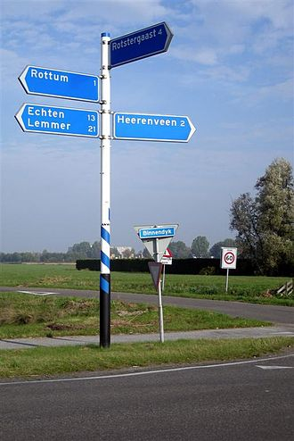 Dutch units of measurement - Signposts showing number of kilometres to nearest towns. A roadsign showing the speed limit in kilometres an hour is visible in the middle distance.