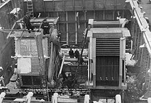 A cavernous steel room, with two large rectangular boilers inside; a number of men are working on the machines.