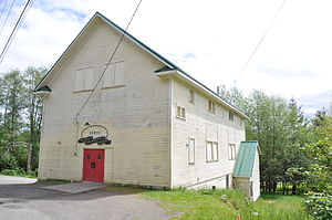 White building with red doors on a hillside