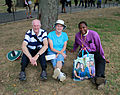 Older couple sitting under a tree with minister in purple shirt and Obama family bag - 50th Anniversary of the March on Washington for Jobs and Freedom.jpg