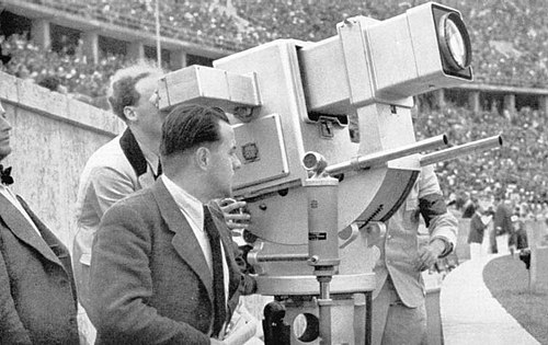 "The ""Olympic Cannon"" television camera at the 1936 Summer Olympics in Berlin, developed by Emil Mechau at Telefunken and operated by Walter Bruch (inventor of the PAL-system.) Olympia-Kanone 1936.jpg"