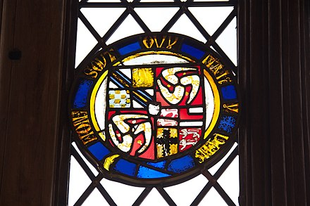 Stained glass at Ordsall Hall, Salford, Lancashire, showing the arms of Stanley: 1st grand quarter: quarterly - 1&4: Stanley; 2: Lathom (erased); 3: de Warenne, Earl of Surrey; 2nd & 3rd grand quarters: King of Man; 4th grand quarter: quarterly - 1&4: Strange of Knockyn; 2: Woodville; 3: Mohun of Dunster Castle, Baron Mohun. All circumscribed by the Garter. Possibly the arms of Thomas Stanley, 1st Earl of Derby (1435-1504), KG Ordsall Hall 2014 04.jpg