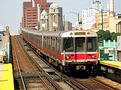 A silver and red rapid transit train departing an above-ground station