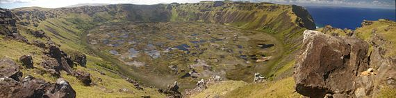 Colour photo of circular pond strewn marsh surrounded by steep cliff topped slopes - the sea is visible through a gap in the cliffs on the right