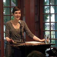 A caucasian woman with short hair lecturing at a podium