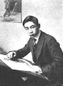 Black-and-white photograph of a man posed at a drawing board