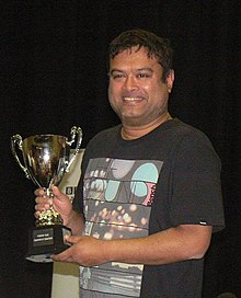 Paul Sinha holding the Fighting Talk Champion of Champions Trophy (cropped).jpg