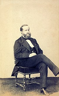 Photograph of a seated, bearded man dressed in a dark suit and vest