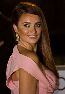 In the photo, Penélope Cruz wearing a pink dress and gold earrings can be seen. She has medium brown hair, the rest of her hair is down in front of her chest while turning her head to her right