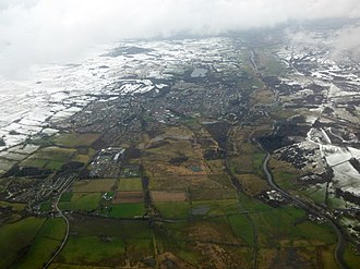 Kilsyth - Queenzieburn and Kilsyth from the air. The four main vertical lines looking roughly eastwards at the bottom of the picture are: Glasgow Road through Queenzieburn and Kilsyth, the line of the old Kelvin Valley Railway Line near Gavell Station, the River Kelvin, and the Forth and Clyde Canal