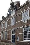 foto van Royaal huis met verhoogde middenpartij door fronton gedekt. Hijsluik en balk. Natuurstenen blokken boven de ramen