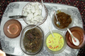 four dishes traditionally eaten during Hari Raya Puasa or Hari Raya Haji are seen laid out on a table.