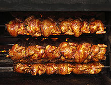 Six golden-brown whole chickens are being roasted on each of three black metal spits.