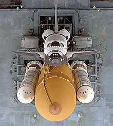 An overhead view of a spaceplane, coloured white on its topside and black on its underside, attached to a large orange tank, to which two slender white rockets are also attached. A gray platform supporting this stack serves as the background.