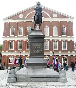 "A statue on a pedestal of a man standing with his arms crossed. An inscription on the pedestal reads, ""Samuel Adams, 1722–1803. A Patriot. He organized the Revolution and signed the Declaration of Independence."" Behind the statue is a three story brick building with many windows."