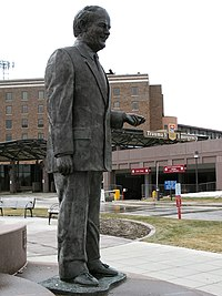 A bronze statue of a late middle-aged man holding up his hand at waist level.
