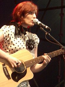 29-year-old Blasko is shown in an upper body shot. She is leaning and singing into a microphone on its stand to her left while looking forward. She is holding her guitar with her right hand plucking the strings and her left low on the fret board. She wears a cream-coloured dress with dark polka dots. She wears a dark, twisted ring on her right middle finger.