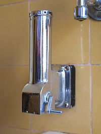 A vertical stainless steel tube, mounted on a wall, with a crank handle on the side at the bottom, next to the hopper-like horizontal opening from which the grated soap will fall