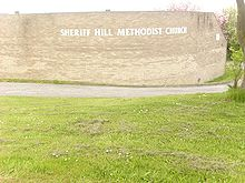 "Behind a large area of mown grass stands a beige brick wall which curves around a corner to the right. The wall bears the words ""Sheriff Hill Methodist Church"", which follow the curve of the wall."